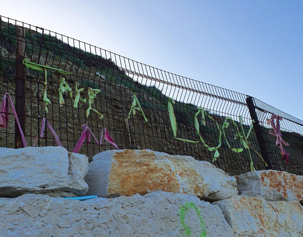 על גדר, בחוף הים ביפו, מישהי או מישהו יצרו כרזה מבדים שבה כתוב Take a Look